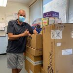 Volunteer Matt stands with boxes full of donations he gathered to create care packages for campers.