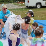 Nichol sprays foam for a group of campers playing during Silly Olympics.