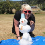 """Nichol with a tiny snowman at Summer Camp, titled, """"who else could make it snow in July at camp?"""""""